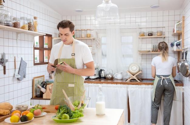 自宅のモダンなキッチンで料理をして幸せな白人カップル家族。女性はシンクで皿を洗う