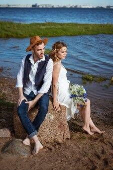 그녀의 손에 꽃의 꽃다발을 들고 해변 여름 날에 행복 한 백인 커플 남자와 여자