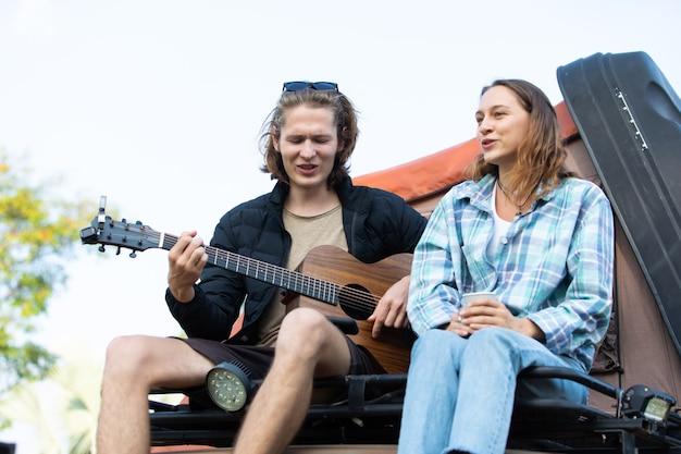 Счастливая кавказская пара играет на гитаре на фоне автомобиля палатки