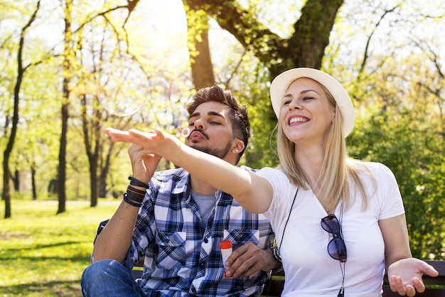 공원 벤치에 앉아 거품을 불고 즐거운 시간을 보내는 행복한 백인 커플