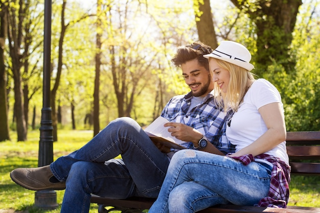 Happy caucasian couple sitting on a park bench, reading a book together