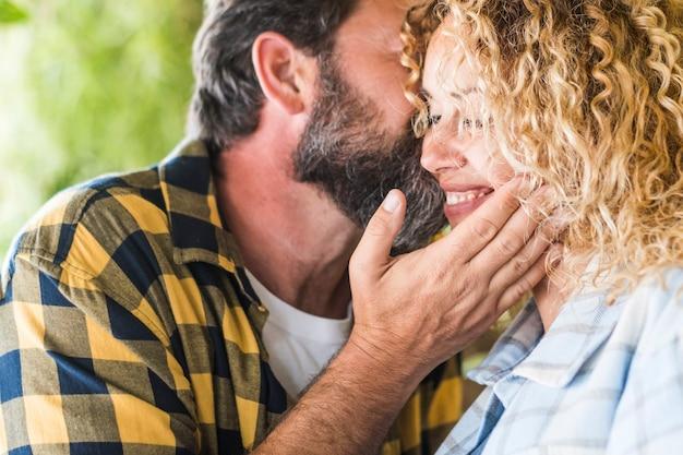 家で一緒に余暇を過ごす幸せな白人カップル。彼女の妻にキスするロマンチックな夫のクローズアップ。愛情のこもった愛情のあるカップル、妻にキスする男