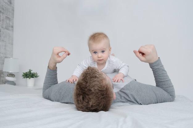 Счастливый кавказский милый ребенок, лежащий на отце, изумленный взгляд камеры на кровати в белом сером интерьере дома.