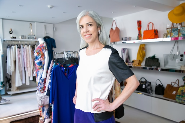 Felice caucasica donna dai capelli biondi in piedi vicino a cremagliera con abiti nel negozio di vestiti, guardando la fotocamera e sorridente. cliente boutique o concetto di assistente di negozio