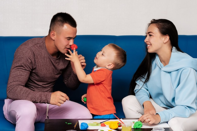 Happy caucasian family are engaged in creative work at home and have fun. mom, son and dad sculpt with clay and paint at the table