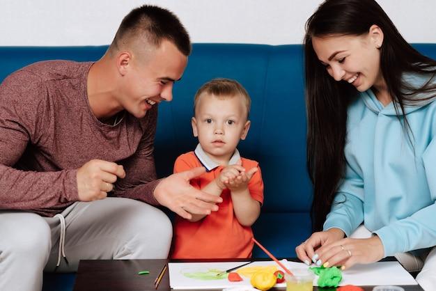 幸せな白人家族は自宅で創造的な仕事に従事していて、楽しんでいます。ママ、息子、パパはテーブルで粘土と絵の具で彫刻します