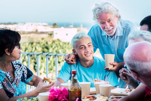 幸せな白人家族は、友情の中で若いティーンエイジャーから古いシニア祖父までさまざまな年齢の人々と一緒に祝います