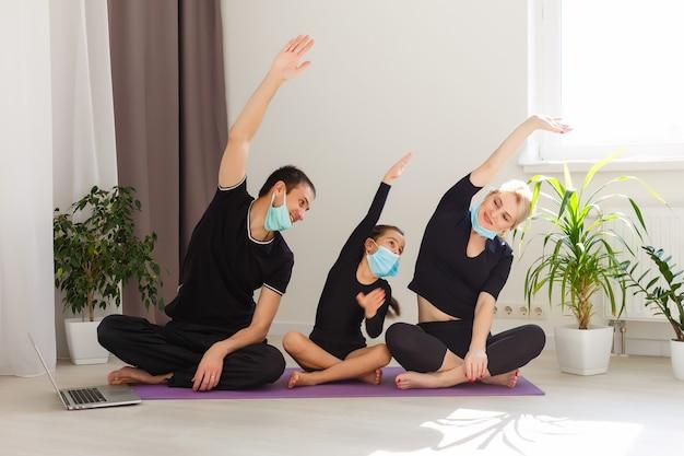 朝のアパートで一緒にフィットネスをしている幸せな白人家族。免疫予防コロナウイルスの流行