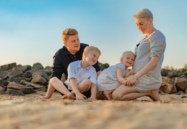 幸せな白人家族は、女の赤ちゃんがお母さんの腹に触れることを期待しています