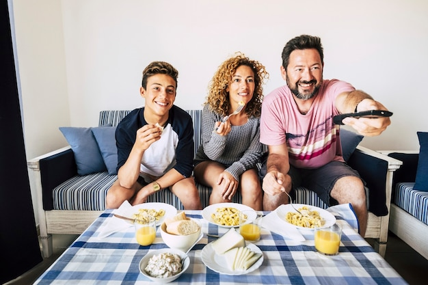 Happy caucasian family have lunch together at home, watching tv