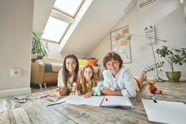 自宅のリビングルームの床に横たわって、カメラの母に微笑んで幸せな白人家族