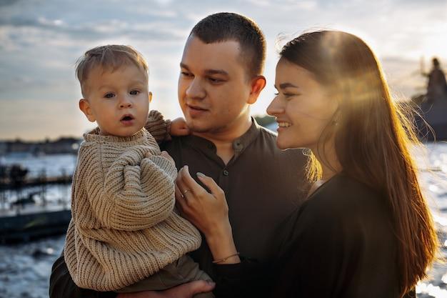 행복한 백인 가족: 부두에서 엄마, 아빠, 아기. 부모는 아들을 보고 태양을 곁눈질합니다. 선택적 포커스가 있는 이미지입니다. 고품질 사진