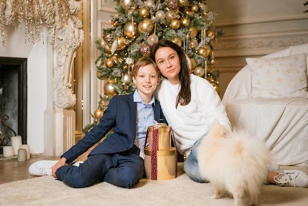 幸せな白人家族の母と息子は彼らの小さな犬の家族と一緒にクリスマスツリーの近くに家で座っています...