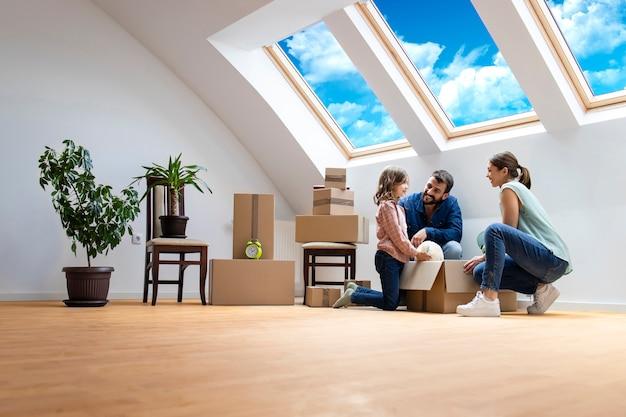 행복한 백인 가족이 새 아파트로 이사하고 함께 상자를 풀고 있습니다.