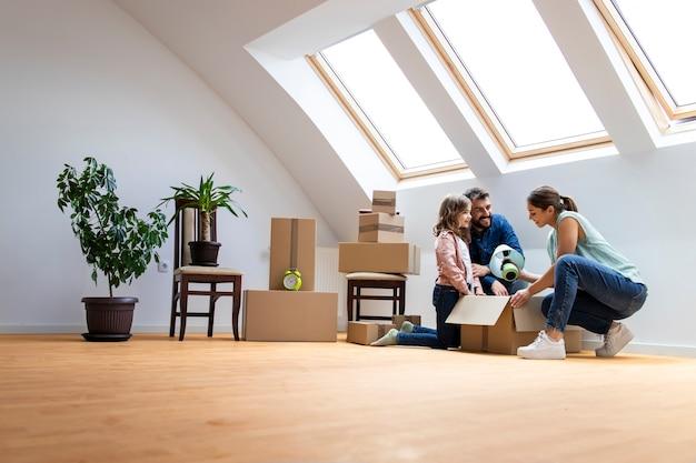 행복한 백인 가족이 새 집으로 이사하고 함께 상자를 풀고 있습니다.