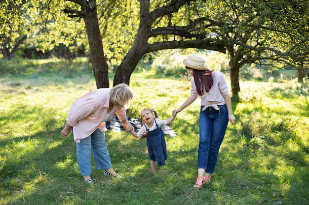 A happy caucasian family of three generations, grandmother, daughter, and little kid girl, walking outdoors in sunny park and having fun.