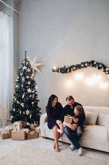 Happy caucasian family of three sit on the sofa next to the christmas tree together