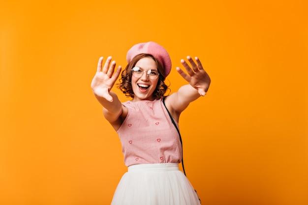 カメラを笑い、手を振ってベレー帽の幸せな白人の女の子。黄色の背景でポーズをとるかなり若い女性のスタジオショット。