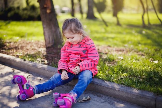 夏の日の公園の道路でローラースケートに乗ってピンクのジャケットを着た幸せな白人の女の子。季節のアウトドアキッズアクティビティスポーツ。