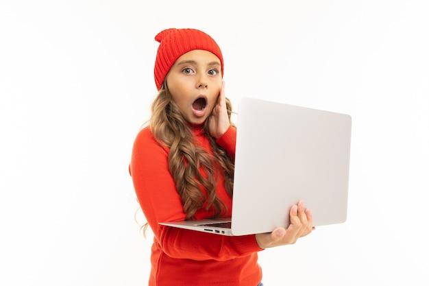 赤い帽子と白い背景で隔離のラップトップでフーディサーフィンインターネットで幸せな白人少女