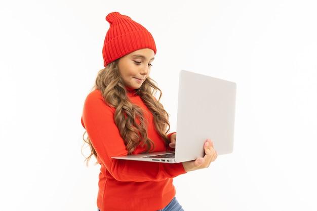 赤い帽子と白で隔離のラップトップでフーディサーフィンインターネットで幸せな白人少女