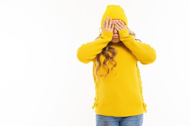 黄色い帽子とフーディで幸せな白人少女は、白い背景で隔離された彼女の目を閉じた