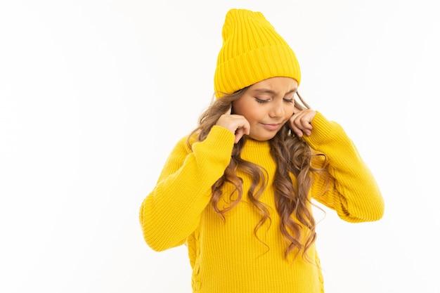 黄色の帽子とフーディで幸せな白人少女は白で隔離を聞きたくないです。