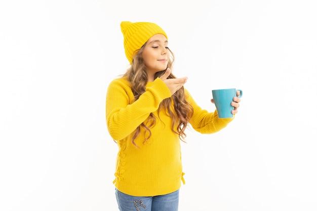 イエローハットとフーディドリンクお茶や白で隔離されるコーヒーで幸せな白人少女