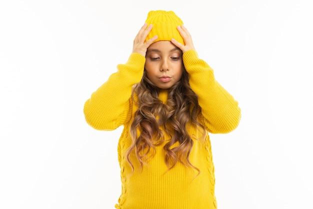 黄色い帽子とフーディで幸せな白人の女の子は白で隔離される驚き