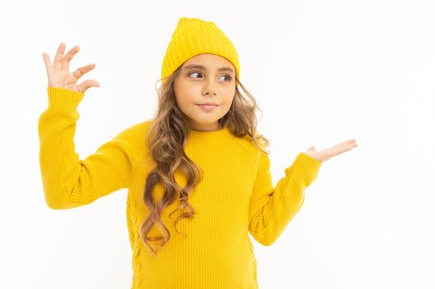黄色い帽子とフーディで幸せな白人少女は白い背景に分離された少しを示しています