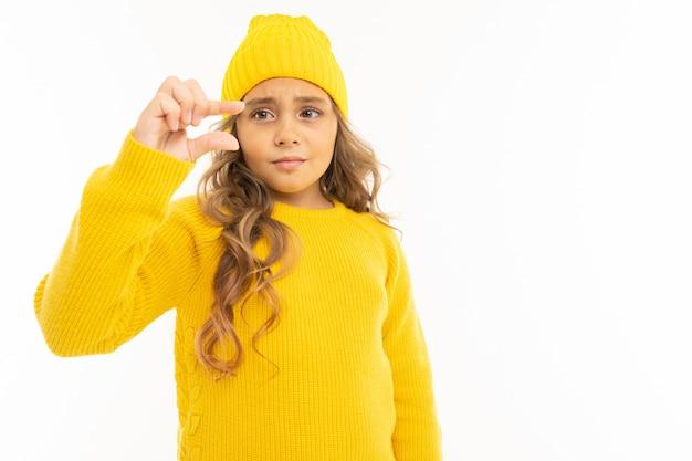 黄色い帽子とフーディで幸せな白人少女は少し白で隔離を示しています