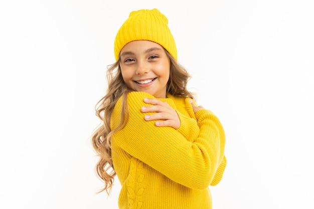 黄色の帽子とフーディの笑顔で幸せな白人少女と白い背景で隔離の喜び