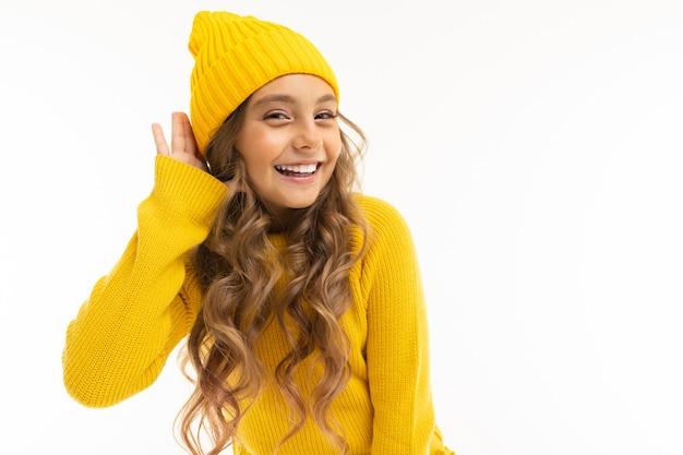 黄色の帽子とフーディの笑顔で幸せな白人少女と白で隔離される喜ぶ