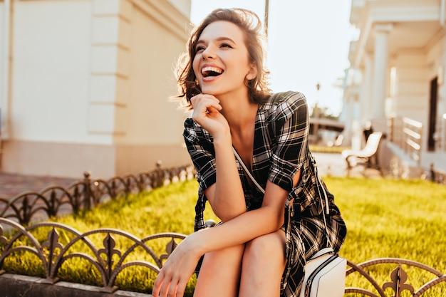 公園でポーズをとっている間、遠くを見ている幸せな白人の女の子。晴れた秋の朝を楽しんでいる市松模様の服装で洗練された短い髪の女性。