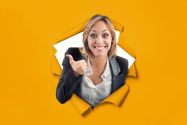 엄지손가락을 들고 행복한 백인 소녀가 노란 종이 배경의 구멍에서 나온다
