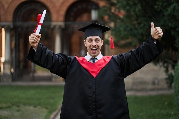 卒業式のガウンで幸せな白人の大学院生は、キャンパスで卒業証書を保持しています。