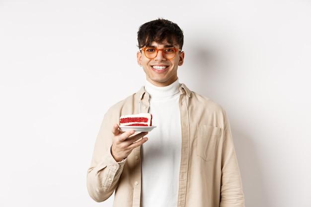 Felice ragazzo caucasico che festeggia il compleanno, tiene in mano una torta con una candela e sorride allegro alla telecamera, in piedi su sfondo bianco