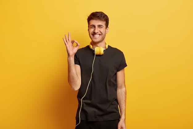 Счастливый кавказец показывает нормальный жест, с чем-то соглашается, утверждает, что все в порядке, широко улыбается, носит наушники на шее