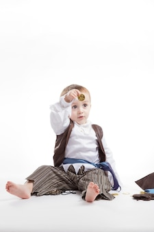 Happy caucasian little boy, dressed as a pirate playing with coins and confetti. little boy and costumes concept.