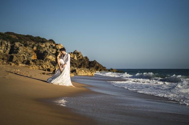 Coppie amorose caucasiche felici che indossano abbracci bianchi in spiaggia durante un servizio fotografico di matrimonio