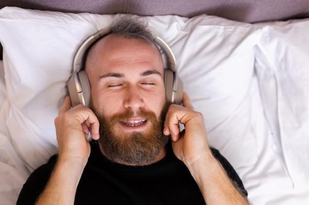 Happy caucasian man on bed wearing headphone listen enjoy his favorite music, resting alone, dancing.