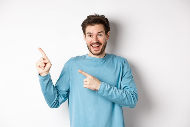 Happy caucasian man in casual blue sweatshirt, pointing fingers at upper left corner, showing link or logo on white background, smiling at camera.