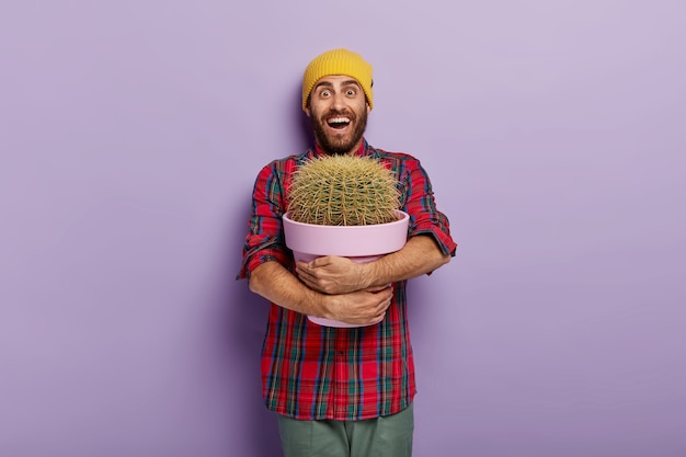 Happy caucasian man embraces pot with big cactus, being plant lover, receives indoor plant as present