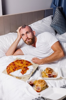 행복 한 백인 남자가 침대에 침실에서 집에서 패스트 푸드를 가지고 온라인으로 음식을 주문하고 편안한 방에서 피자와 햄버거를 먹습니다.