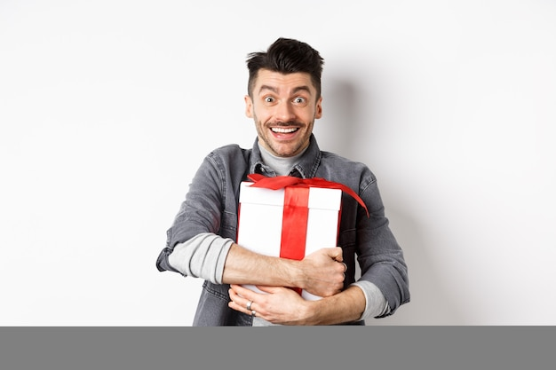 Happy caucasian man holding surprise gift, hugging present and smiling thankful, looking at camera with love and appreciation, celebrate valentines holiday, white.