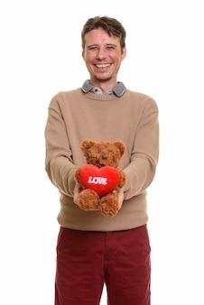 Счастливый кавказский мужчина держит плюшевого мишку с сердцем и знаком любви