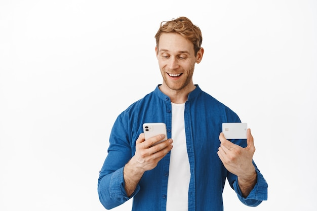 Happy caucasian man looking at smartphone while paying online with credit card, making order in mobile app, shopping in internet with bank card and cellphone, standing over white wall