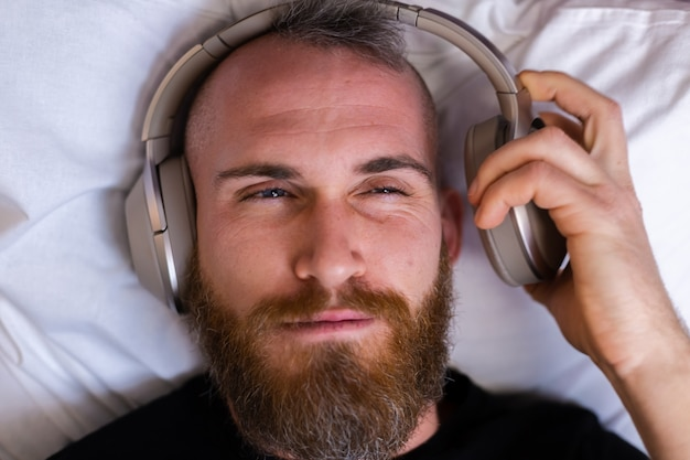 ヘッドフォンを身に着けているベッドの上の幸せな白人男性は、彼の好きな音楽を楽しんで、一人で休んで、踊っています。