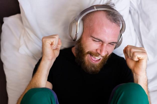 헤드폰을 착용 침대에 행복 백인 남자는 혼자 쉬고, 춤을 좋아하는 음악을 즐길 수 있습니다.