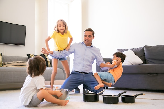 Happy caucasian man playing with children and showing strength. cheerful kids having fun together in living room on carpet. pans and bowl for game. childhood, weekend and home activity concept